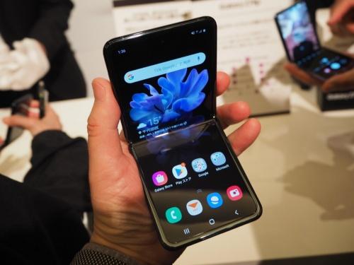サムスン電子が2020年2月に発表した「Galaxy Z Flip」。「Galaxy Fold」とは異なりディスプレーを縦に折り畳むスタイルのスマートフォン。日本ではKDDIが販売する。写真はKDDIが2020年2月17日に開いたau新商品・サービス発表会より