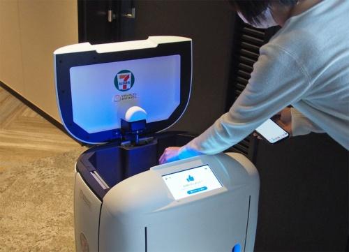 RICEが到着したらスマートフォンにSMSで送られた暗証番号を入力してロックを解除し、蓋を開けて商品を受け取る。写真は2021年4月20日にセブン‐イレブン・ジャパンらが実施した自律走行型ロボットによる商品配送の実証実験より(筆者撮影)