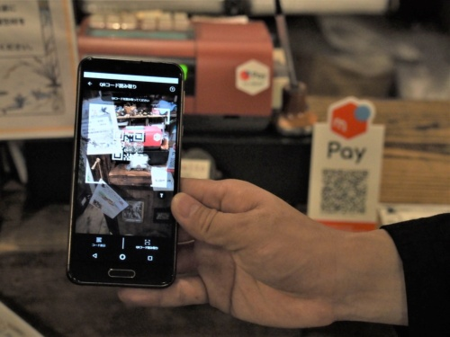 顧客がQRコードを読み取って決済するMPM方式は、専用の機材が不要でQRコードを置くだけと導入しやすいことから、主に中小店舗で多く導入されている。写真は2019年7月26日、「高円寺メルペイ通り」が展開されていた東京・高円寺の店舗にて(筆者撮影)