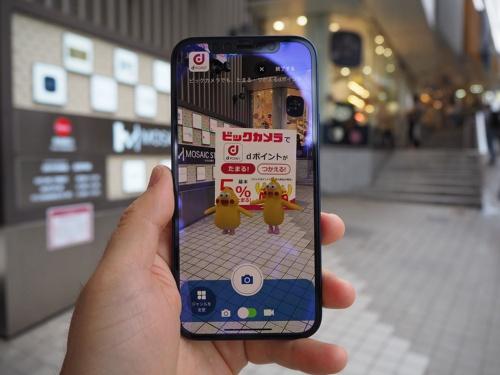 「XRシティ SHINJUKU」の第2弾イベントでは、新宿駅周辺の特定スポットで専用アプリを起動し、スマートフォンをかざすと様々なコンテンツを楽しめる。写真は「キャラ」を体験しているところ。写真は2021年6月23日に実施された同イベントの体験会より(筆者撮影)