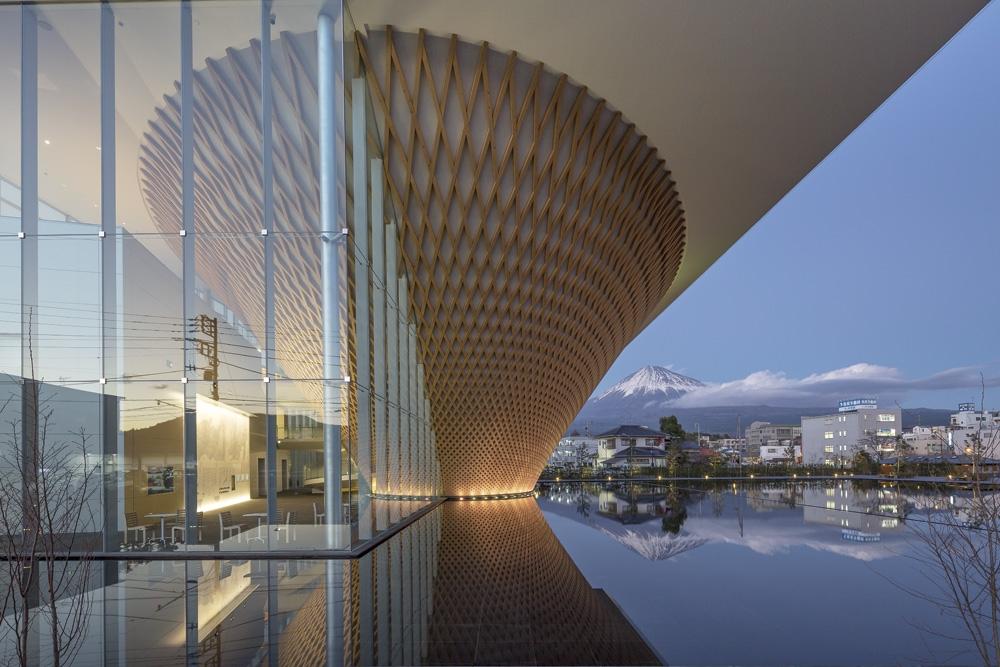 JR身延線・富士宮駅に続く県道414号側から見る。設計者の坂茂氏は、2014年の静岡県による公募型設計プロポーザルで選ばれた。13年に世界文化遺産となった富士山の情報を発信する拠点施設としての象徴性を考慮し、逆さ富士の形を持つ展示室を提案した(写真:平井 広行)