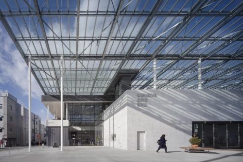 大きなガラス屋根が架かる北広場。半屋外の空間は、人を大型商業施設から商店街へ誘導する役割を担う。平土間仕様のセッティングとして、右下のホール開口部を開放すれば、広場から奥の大きなホールまで床がフラットにつながる(撮影:吉田 誠)