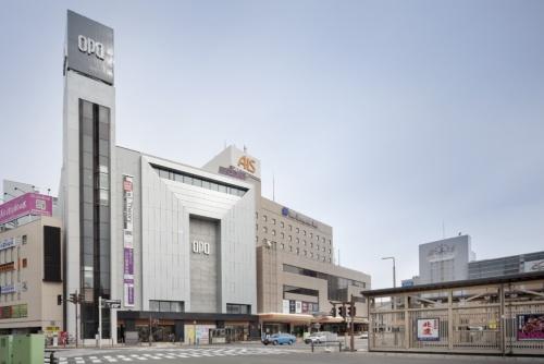 JR秋田駅の駅前広場から見た南側全景。フッ素樹脂塗装したアルミ板でコの字に囲まれた内側に、高さ6層分のコンクリート打ち放しの耐震壁が立ち上がる。写真左側に見えるエレベーター部分は既存のままだ。1974年完成の建物を、耐震補強を含めて全館リニューアルし、2017年10月28日にオープンした(写真:吉田 誠)