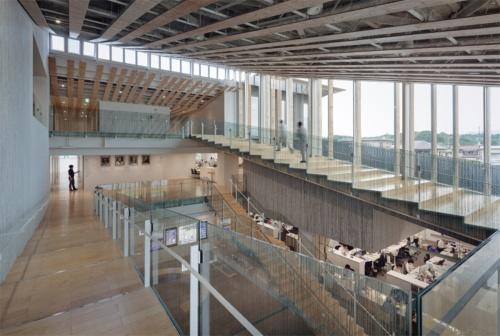 行政棟のエントランスまわりは3層吹き抜け。2階と3階をつなぐ階段からは街の風景を眺められる。壁面に張られているのは、「きびそ」と呼ばれる生糸を用いた壁紙。ガラスの手すりには、きびそをスキャンした柄をランダムに組み合わせたセラミックプリントを施した(写真:吉田 誠)