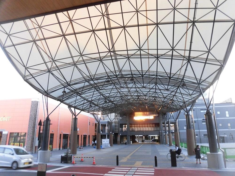 図書館からまちなか広場越しに複合施設を見る。道路をまたいで屋根が架かる(写真:日経アーキテクチュア)