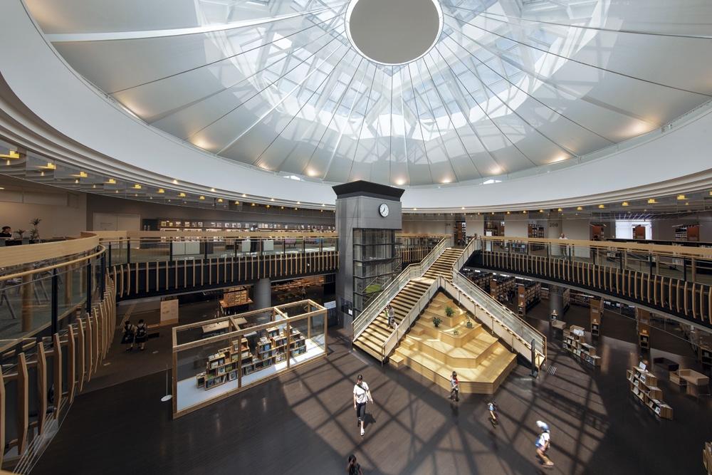 ショッピングモールを改修し、4月28日に開館した都城市立図書館。時計塔は既存のものを生かした。広場にあった既存のエスカレーターを撤去して、2またの階段を架けた(写真:イクマ サトシ)