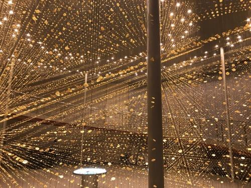 """12月16日(日)まで開催中のシチズン時計創業100周年イベント「CITIZEN""""We Celebrate Time""""100周年展」のメイン展示。「LIGHT is TIME」と題したインスタレーション。吊られている金色のものは?(写真:日経アーキテクチュア)"""