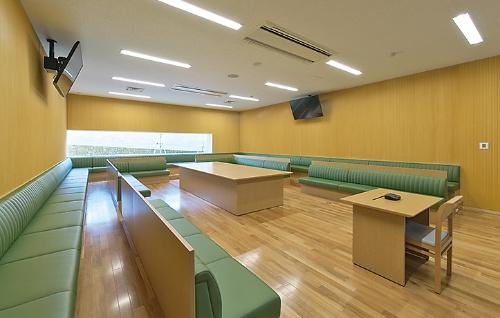 1階のディスカッションラボ。各席に机のない英国議会をモチーフにしたレイアウトで学生同士の白熱した議論を促す。計60席(写真:生田 将人)