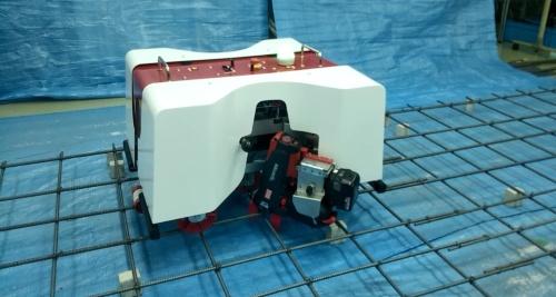 EMOとサンエスが共同で開発した鉄筋結束ロボット「トモロボ」。写真は実証の様子。鉄筋を配した上を自律走行し、交差部を結ぶ(写真:EMO)