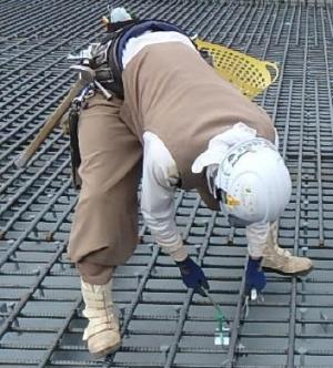 鉄筋の結束は中腰での作業が続くため、作業員の負担が大きい(写真:EMO)