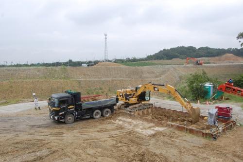 土砂置き場から土砂を掘削してダンプトラックに積む作業を自動化している。油圧ショベルにオペレーターは乗っていない(写真:日経 xTECH)