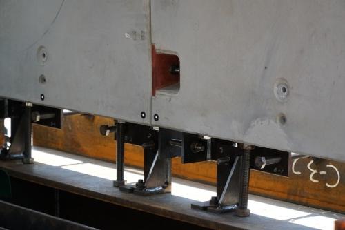 PCa部材のトンネル縦断方向の連結部と下端の調整部。縦断方向はオス側のピンをメス側のソケットに差し込む「リング間継ぎ手」で連結する。横断方向はC形金具とH形金具をかみ合わせる「ピース間継ぎ手」を採用した。PCa部材は、側壁コンクリートを模したH形鋼の上に設置してある。専用治具やボルトを介して位置を調整し、PCa部材の設置後は治具をモルタルなどで埋める(写真:日経コンストラクション)