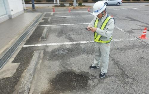スマートフォン用アプリ「ポットホールメジャー」のカメラ機能で撮影している様子(写真:東亜道路工業)