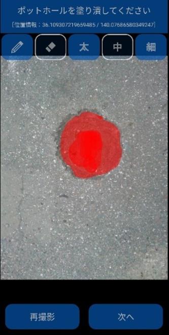 スマホに表示される画像のポットホール部分を塗りつぶすと赤色になる(資料:東亜道路工業)