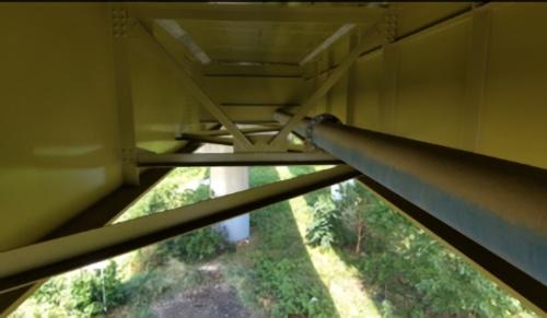 橋の床版下面を飛行する様子。管路や対傾構が密に配置された狭い空間でも難なく飛行できる(写真:ジャパン・インフラ・ウェイマーク)