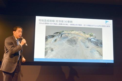 実際に測量したデータについて説明する佐部社長。長崎県佐世保市の約50haの造成現場では、2800枚の画像を1日で撮影し、6時間以内で解析。全ての検証点で5cm以内の精度を実現した(写真:日経クロステック)