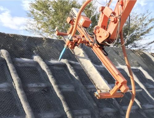 自動スライドノズル。法面とノズル先端の距離は1mに保つ。法面と平行に自動スライドノズルを動かせるので、一様な幅や長さ、厚さの吹き付け枠を容易に構築できる(写真:大林組)