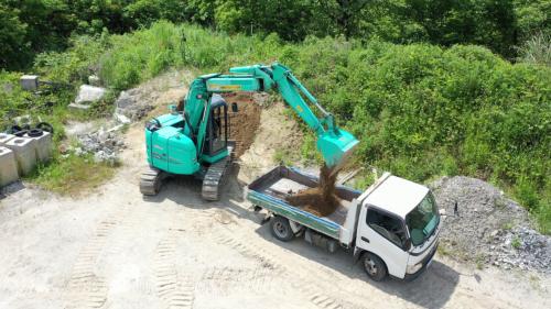 遠隔操作によって油圧ショベルで土砂をダンプトラックに積む様子(写真:ARAV)