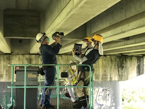 SenrigaNによる計測の様子。写真左の作業者が計測装置を桁の下面に当てている。それを右手前の作業者がタブレット端末で撮影し、オンラインで専門家の指示を仰ぐ。「内閣府オープンイノベーションチャレンジ2019」に採択され、調査・点検会社のSXR(香川県丸亀市)と共に福岡市のPC桁橋で効果を検証した。2020年7月に撮影(写真:コニカミノルタ)
