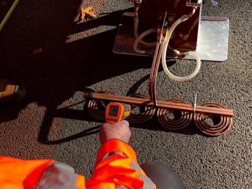 オランダで自己治癒型のアスファルト舗装を施工してから5年後に、供用状況を確認している様子。舗装表面に特殊機器を当てて加熱するだけで、劣化を修復できる(写真:山田 敏広)