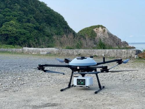 沖縄県竹富町の西表島で実証実験に使ったハイブリッドドローン。グリーンレーザースキャナーは、アミューズワンセルフ製の「TDOT GREEN」。小川精機が開発したドローン搭載型発電機によって給電する(写真:アミューズワンセルフ)