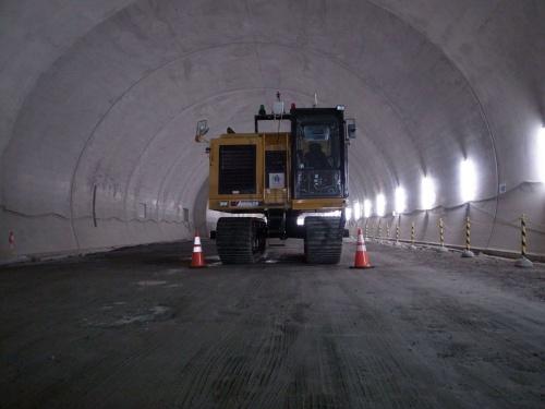 未舗装のトンネル坑内を無人のダンプが走り抜ける。実証中は遠隔操作室から監視していた(写真:大成建設)