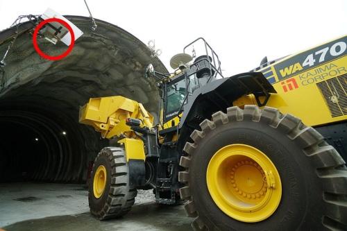 ホイールローダーがトンネル坑内に進入する様子。赤丸で囲んだのがiGPSのレーザー送信機。風雨に弱いため保護している(写真:日経クロステック)