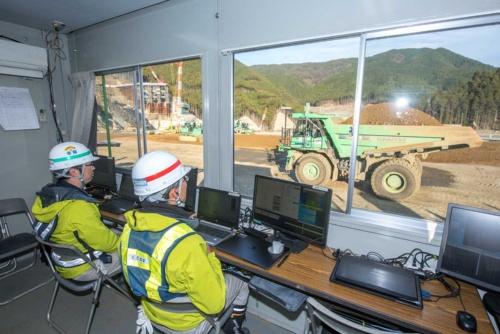 ダム堤体上に設けた管制室。建機に施工開始を指示した後は、動きを監視するだけ(写真:大村 拓也)