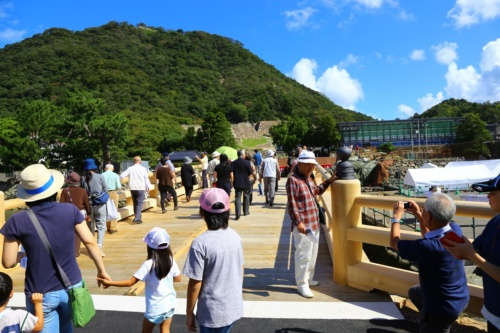 2018年10月8日に開かれた擬宝珠橋の完成式の様子。2000人の市民が渡り初めを楽しんだ。橋の名前の由来となった写真右側の擬宝珠(高欄の上に設けられている飾り)も、現存していた1つを基に忠実に復元。12基設置した(写真:鳥取市)