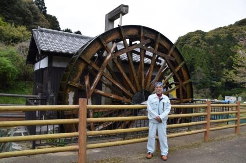 野瀬代表。後ろは自身が造った福岡県久留米市の一ノ瀬親水公園の動力水車。水車小屋の中には、屋外の水輪と連動して動く歯車やシャフト、きね2本と挽臼1基がある(写真:大井 智子)