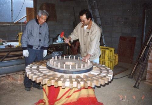 野瀬代表(右)と師匠の中村忠幸氏。動力水車の作業機部分となる歯車を製作しているところ(写真:野瀬建設)