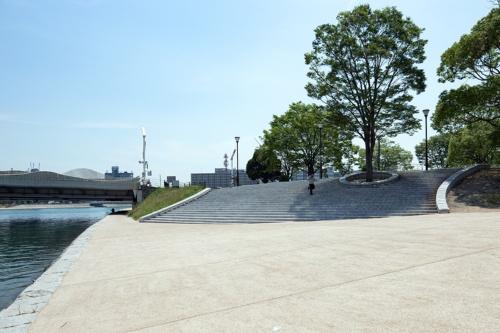 勝山公園と水辺の遊歩道の間に大階段を整備して、川への見通しの良さと動線を確保した。ベンチを兼ねた大階段は、お祭りの時は観覧席になる。写真左は中の橋(写真:イクマ サトシ)