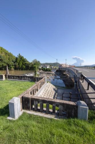 旧山田橋の橋詰め付近に整備した「やまだばし思い出テラス」(右岸側)。写真左側の高さ約3mの親柱は当時の位置のまま両岸に残し、旧橋の高欄を転落防止柵として再利用した。右は新山田橋(写真:イクマ サトシ)
