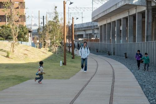 鉄道高架化で生じた線路跡地に、大分市産のスギのデッキ材に古いレールを組み合わせた「線路デッキ」を敷き詰めた(写真:イクマ サトシ)