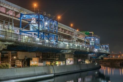 堀切JCT―小菅JCT間で拡幅用の主桁を架設している様子。青い鋼材の枠が「吊りフレーム」(撮影:大村 拓也)