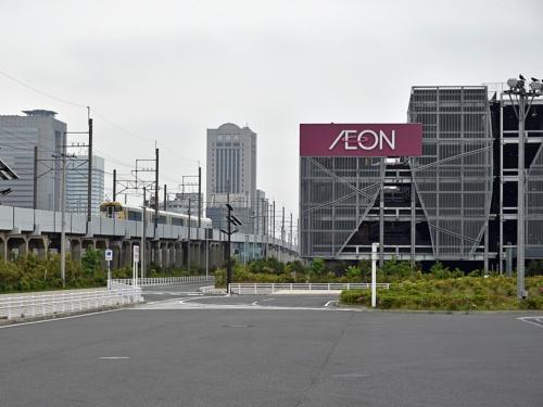 幕張新駅の予定地付近を走るJR京葉線の特急列車。大型の立体駐車場や広いバスターミナル(写真手前)が幕張新都心の交通の現況を物語る。左後方に見えるのは海浜幕張駅北側のオフィスビル群(写真:日経コンストラクション)