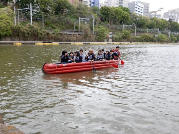 新見附濠(東京都千代田区、新宿区)をEボートで調査する女子高生たち。ボートの漕ぎ手は外濠市民塾メンバーの大学生らが担った。画面奥に浚渫(しゅんせつ)工事用に敷設されたパイプが見える。土手側にはJR中央・総武線線の線路が通っている(写真:三上 美絵)