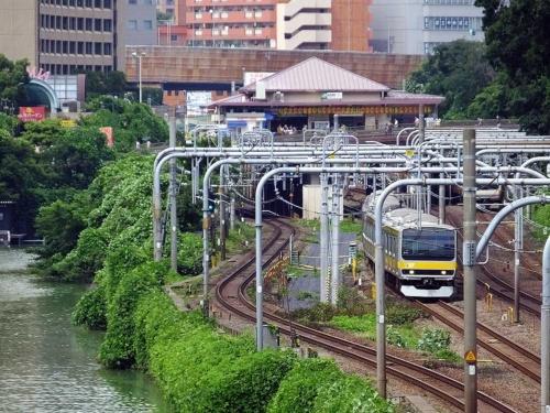 14年7月時点の飯田橋駅西口。黒いビニールシートが敷かれた付近に新ホームを建設する。かつて引き上げ線の線路があった場所だ。正面奥には三角屋根の旧西口駅舎が見える(写真:大野 雅人)