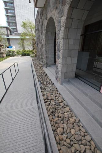 位置をずらしただけでなく、地下室の増築と免震化の工事も実施している。免震のエキスパンションジョイント部分には床石のパネル(写真左端)が敷かれている(写真:日経アーキテクチュア)