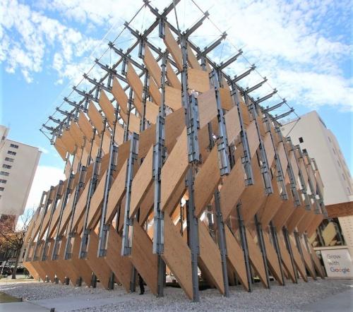 パビリオン棟の外観。建物高さは約18m。2.3m間隔で並ぶ鉄骨柱に厚さ約210mmのCLTパネルをあみだ状に架け渡した。折り紙を連想させる日本らしいデザインを意識している(写真:日経アーキテクチュア)