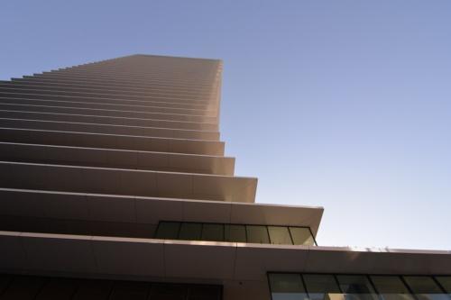 ビジネスタワー北側外観を見上げる。裾広がりのような庇のデザインを強調して、ランドマークとしての視認性を高めた。日射を遮る効果も狙う(写真:日経アーキテクチュア)