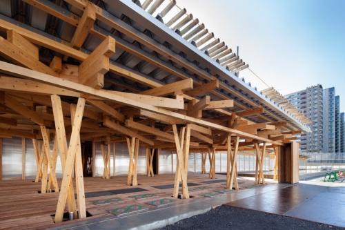 選手村ビレッジプラザのメインエントランス。折板屋根の上には夏の強い日射を緩和するために竹を並べている。エントランス以外の部分では、さらに散水装置を設置し、竹の上から屋根に水をかけて冷やす。水は建物前面の水盤に落ち、涼しさを演出する効果もある(写真:吉田 誠)