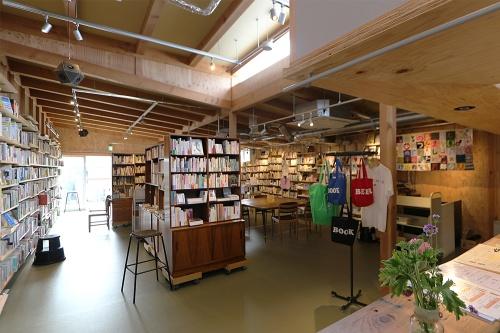 商業棟2階「本屋 B&B」(11)陳列スペース。現在は、オンライン配信を併用する格好としているが、書籍著者のトークイベント開催と飲食サービスをビジネスの一翼とする新刊書店であるため、可動式書棚の並ぶフレキシブルな空間とされている(写真:日経アーキテクチュア)