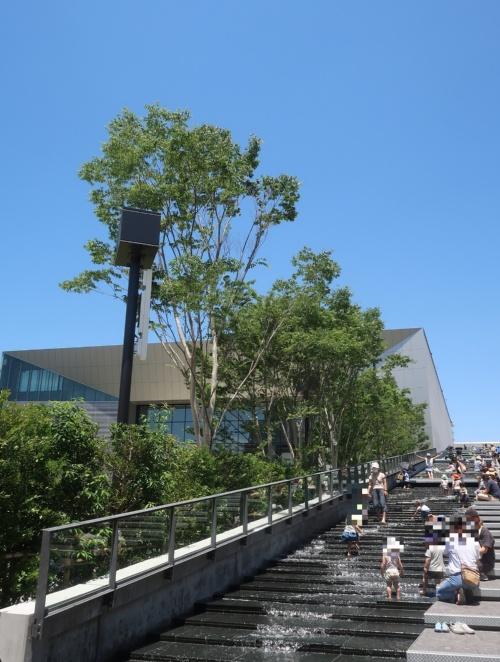 多機能ホールの横には、屋上まで続く長さ約120mの階段状のカスケード(人工滝)がある。早くも子どもたちが水遊びをしている(写真:日経クロステック)