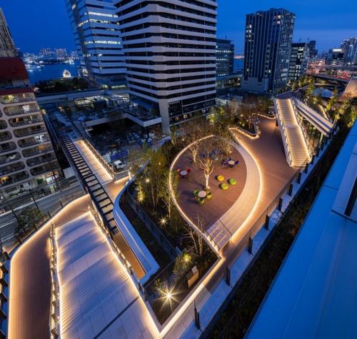 6月30日に竣工したレジデンスタワーを、オフィスタワーのスキップテラス越しに見る(写真:東急不動産、鹿島)