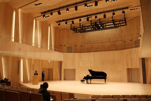 桐朋学園宗次ホールのステージ。壁や天井の照明を取り付けたパネルは音響反射板で、その奥はCLTの現しとした。2階バルコニーの腰壁も音響反射板として機能する。満席時の残響時間は約1.7秒(写真:日経アーキテクチュア)