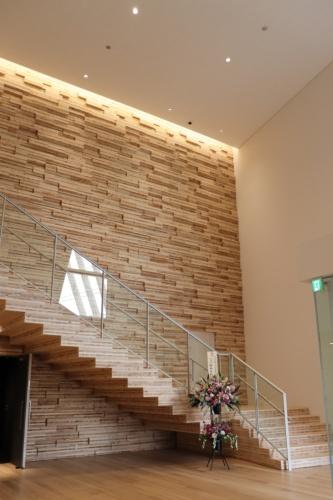桐朋学園宗次ホールのエントランスホール。壁面にはスギとヒノキを使ったハイブリッドCLTの端材をランダムに配置した(写真:日経アーキテクチュア)