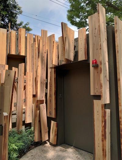 施設は5つに分棟し、各個室の外壁をスギ板のルーバーで覆った。スギ板は耳付きの吉野杉をぜいたくに使い、自然に近づけるようにランダムな角度で取り付けた(写真:日経クロステック)