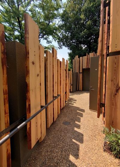 木チップを敷いて固めた小道を通って、5棟を回遊できるようにしている。突き当たりは小便トイレ。隈研吾氏は散策を楽しめるようなトイレづくりを目指したという(写真:日経クロステック)