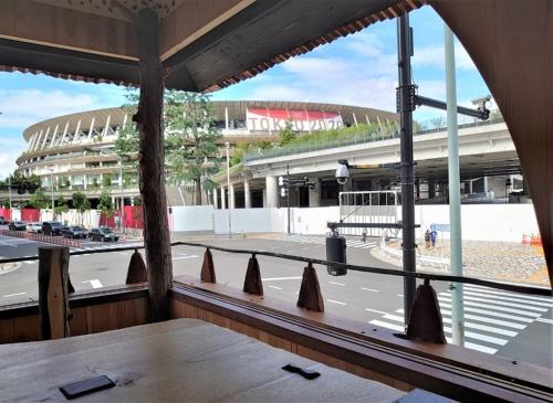 国立競技場の目の前に位置する藤森照信氏のパビリオン「茶室『五庵』」からは、「TOKYO 2020」の文字が間近に見える(写真:日経クロステック)